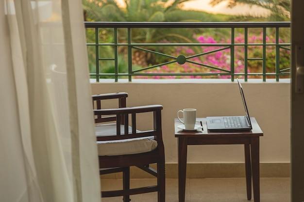 Libero professionista o uomo d'affari che lavora a distanza con il computer portatile sul balcone dell'hotel al resort durante il viaggio. luogo di lavoro senza persone