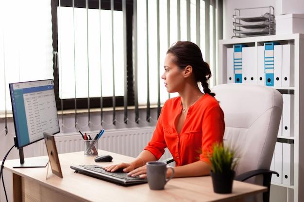 Donna d'affari esecutiva aziendale freelance che lavora sulla strategia di marketing. datore di lavoro concentrato di successo con una carriera impegnata seduto alla scrivania in ufficio utilizzando un pc moderno.