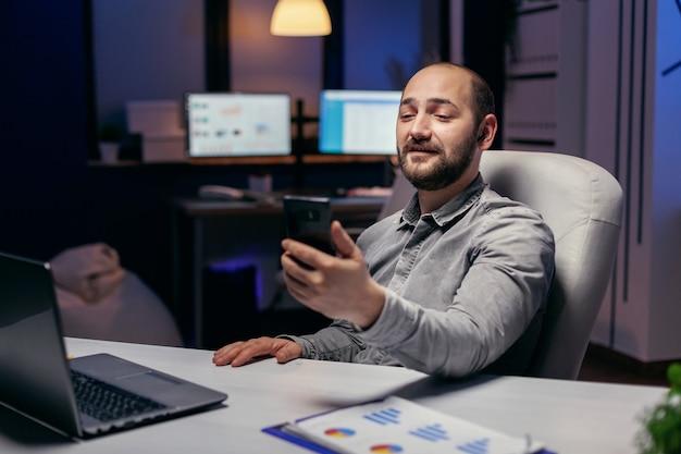 Libero professionista in ufficio vuoto che parla in linea con qualcuno. imprenditore nel corso di un'importante videoconferenza mentre fa gli straordinari in ufficio.