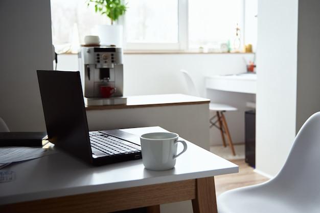 Lavoro domestico libero professionista. computer portatile sul tavolo all'interno dell'ufficio. lavoro online e lavoro a distanza.