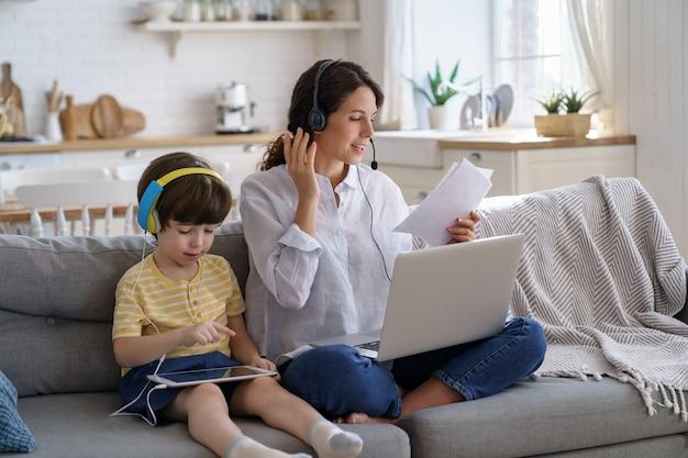 Mamma libera professionista che si siede sul divano a casa durante il blocco lavorando su laptop e bambino che gioca al tablet