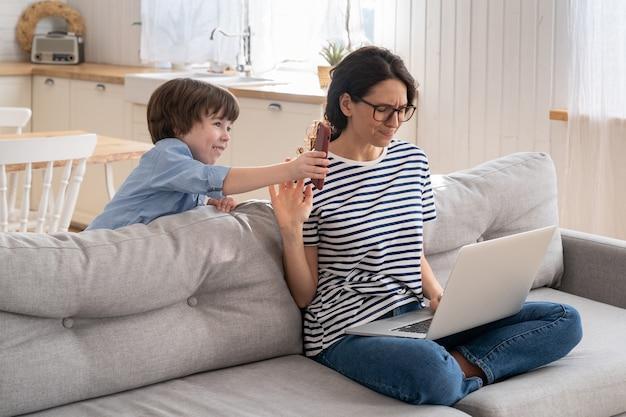 Mamma libera professionista che lavora al computer portatile a casa durante il blocco, il bambino rumoroso distrae chiedendo attenzione.