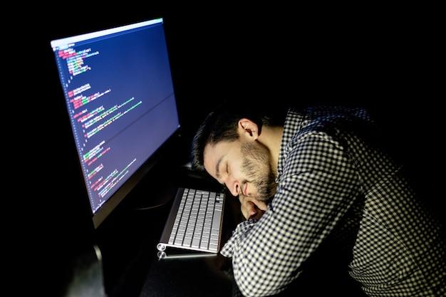 Programmatore libero professionista che cade a faccia in giù facendo un pisolino
