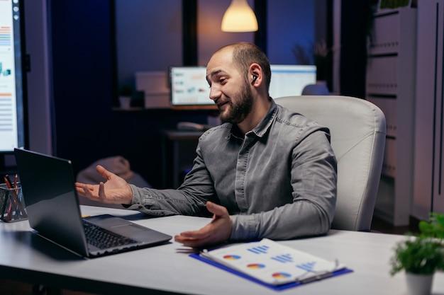 Il libero professionista utilizza le cuffie wireless per parlare con le persone durante una chiamata online. imprenditore nel corso di un'importante videoconferenza mentre fa gli straordinari in ufficio.