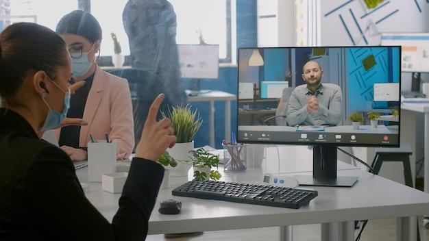 Libero professionista che indossa una maschera protettiva durante la videochiamata online seduto alla scrivania nell'ufficio della società di avvio. colleghi che lavorano al computer durante la pandemia globale di coronavirus
