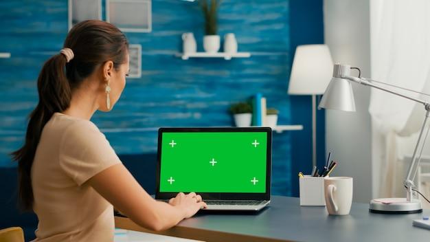 Donna libera professionista che cerca pubblicità aziendale utilizzando un pc isolato in piedi nello studio dell'home office. donna caucasica che lavora con un computer portatile con chroma key schermo verde mock up