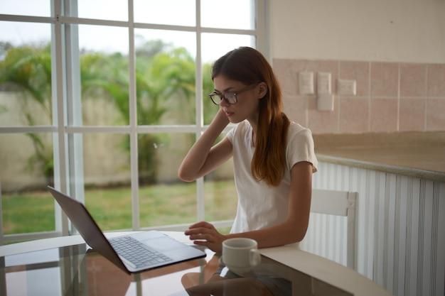 Donna libera professionista con il computer portatile in cucina a lavorare