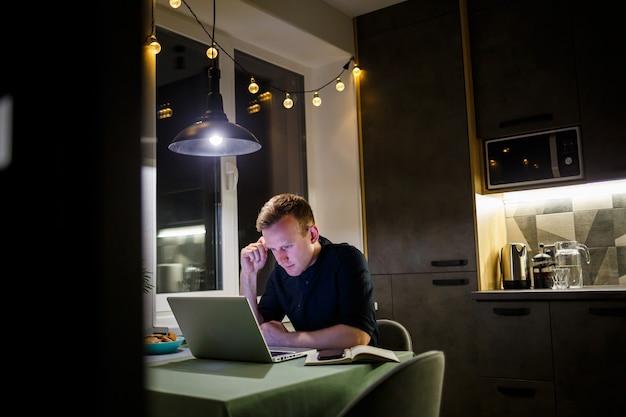 Un libero professionista lavora da casa in cucina e utilizzando un laptop. uomo d'affari che lavora con il computer portatile e legge buone notizie. imprenditore di successo siede e lavora in modo indipendente nella sua casa moderna.