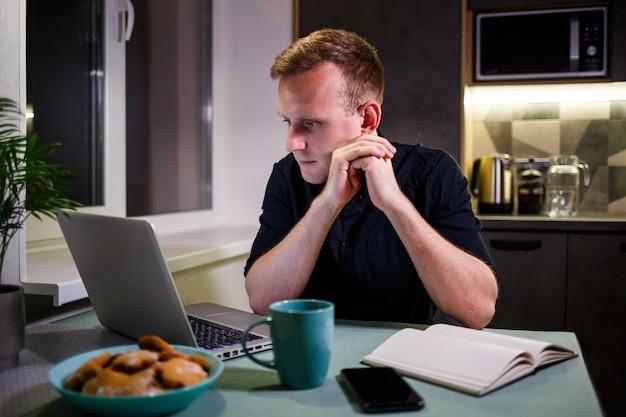Un libero professionista lavora da casa in cucina e utilizzando un laptop. uomo di successo che lavora con un laptop e legge buone notizie. un bell'imprenditore di successo si siede e lavora nella sua casa moderna.