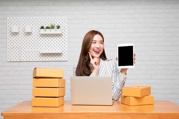 Giovane donna asiatica delle free lance che mostra compressa con la scatola del pacchetto sulla tavola.