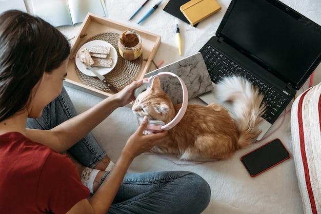 Giovane donna libera professionista che lavora in ufficio a casa con un computer portatile e un gatto che lavora online a distanza