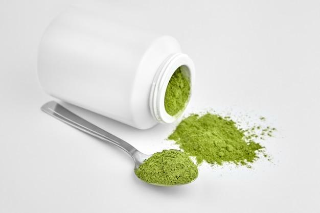 Liofilizzare giovane polvere organica di wheatgrass in cucchiaino e vaso su sfondo bianco