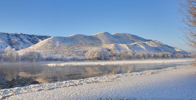 Fiume gelido dalle rive collinari e grandi banchi di ghiaccio. una giornata di sole con un cielo senza nuvole.
