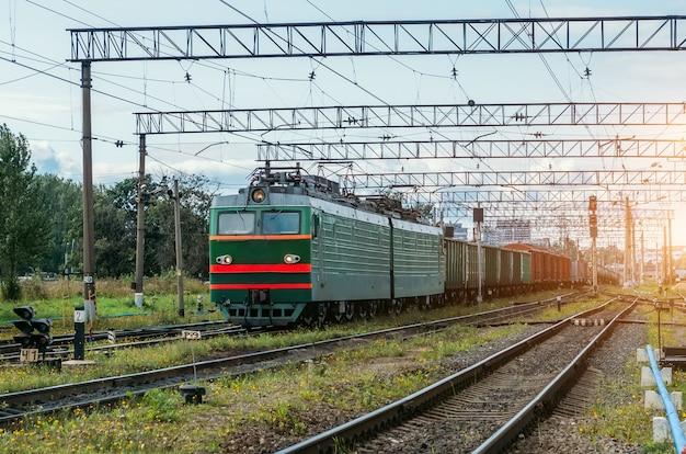 Treno merci verde con vagoni merci sulla ferrovia.