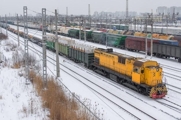 Treno merci allo scalo di smistamento in inverno sulla neve. locomotiva gialla.