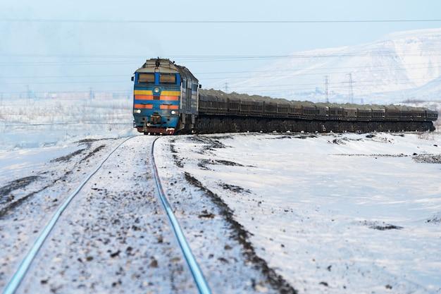 Treno merci in movimento sui binari in inverno