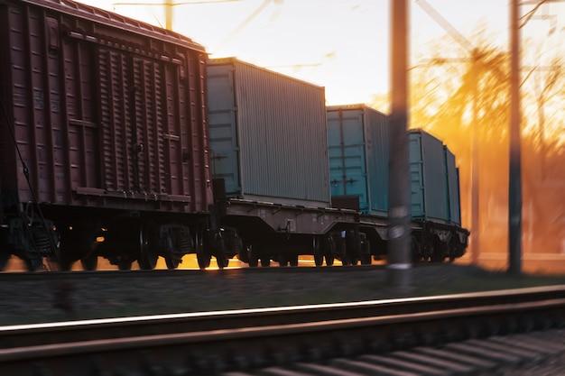 Treno merci che viaggia in ferrovia con effetto sfocato al tramonto.