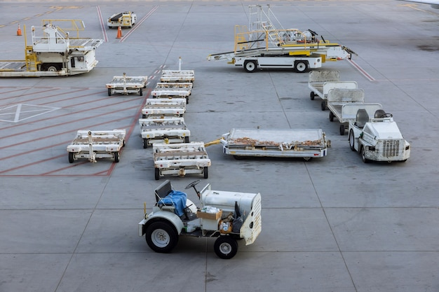 Carrelli merci sulla pista di carico al veicolo di servizio aereo commerciale