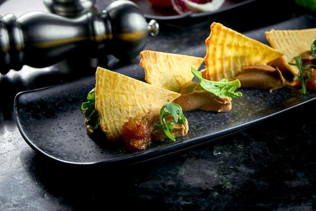 Antipasto francese - patè di pollo con tartine con confit di cipolla servito in un piatto nero su un tavolo di marmo scuro. cibo del ristorante