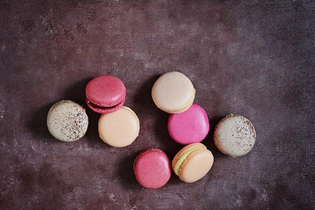 Macarons assortiti francesi agglutina su un fondo grigio