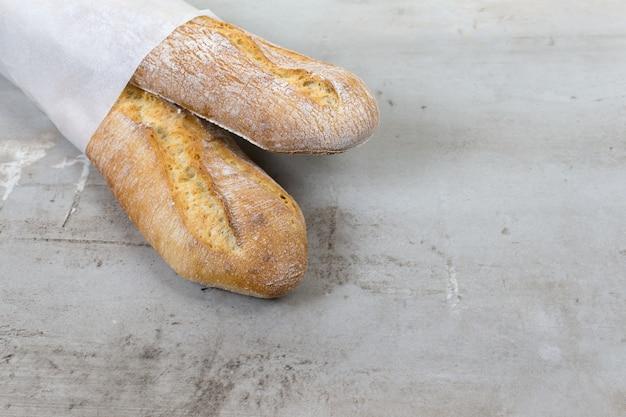 Baguette francesi pane cotto su sfondo tavolo in pietra grigia confezione di carta ecologica