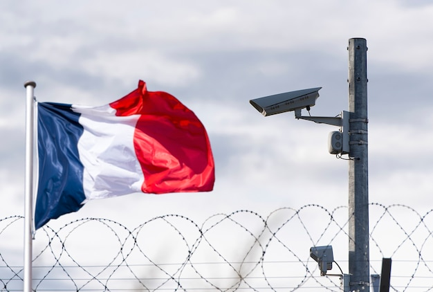 Confine francese, ambasciata, telecamera di sorveglianza, filo spinato e bandiera della francia, immagine concettuale.