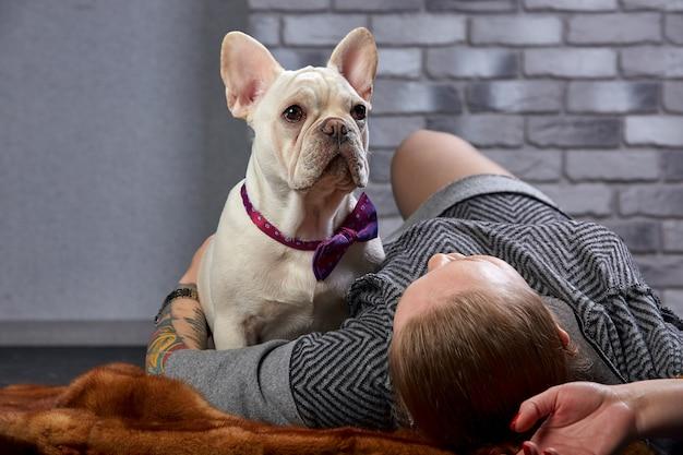 Bulldog francese sulle mani del suo padrone. si ritiene che la donna ami il suo animale domestico e gli abbracci e lo baci forte.