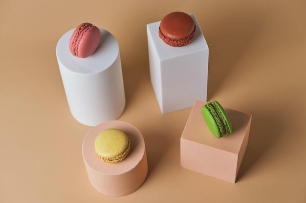 Macarons colorati francesi su piedistalli geometrici alla moda su una superficie beige