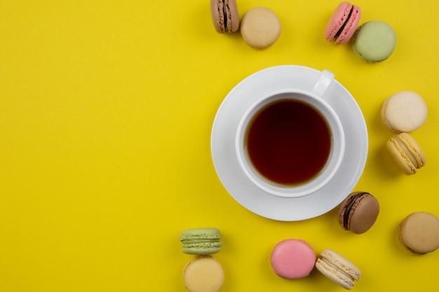 Francese amaretti colorati dessert e una tazza di tè nero o caffè su una superficie gialla