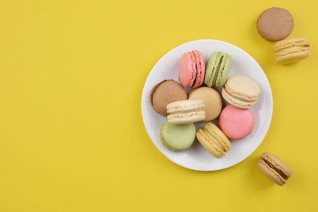 Francese amaretti colorati dessert sulla piastra bianca, superficie gialla