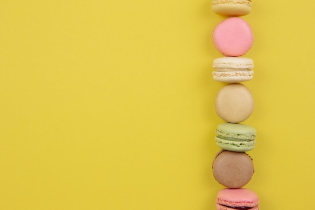 Dessert francese amaretti colorati sulla superficie gialla