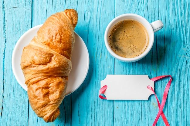 Cartolina d'auguri in bianco della tazza di caffè del croissant francese sulla tavola blu