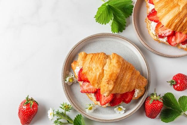 Panino croissant francese con fragole mature fresche e formaggio cremoso in un piatto con fiori su superficie bianca