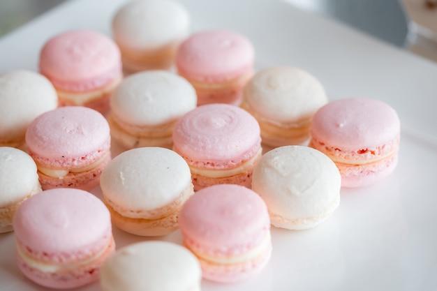 Dessert francese. deliziosi macarons alla fragola e alla vaniglia. dessert di nozze sul tavolo dolce. sfondo pastello morbido.