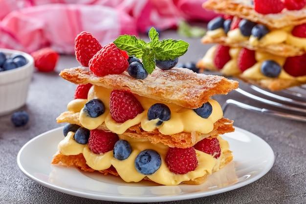Millefoglie di dessert francese di tre pezzi di pasta sfoglia a strati con crema pasticcera, lamponi, mirtilli su una piastra bianca su un tavolo di cemento, vista dall'alto, primo piano