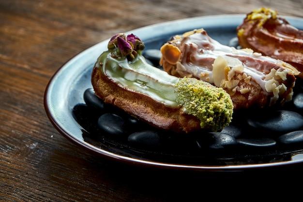 Eclairs francesi con crema pasticcera e condimenti assortiti serviti su un piatto nero su uno sfondo di legno. cibo del ristorante.