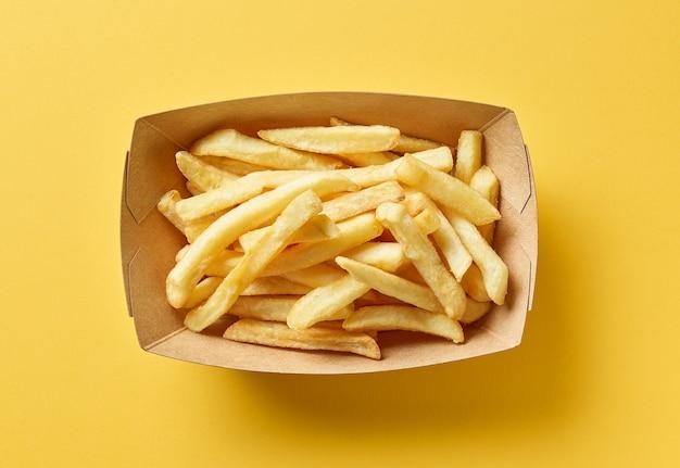 Patatine fritte in contenitore di cartone su sfondo giallo, vista dall'alto
