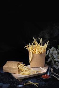 Patatine fritte gialle su fondo nero con fumo