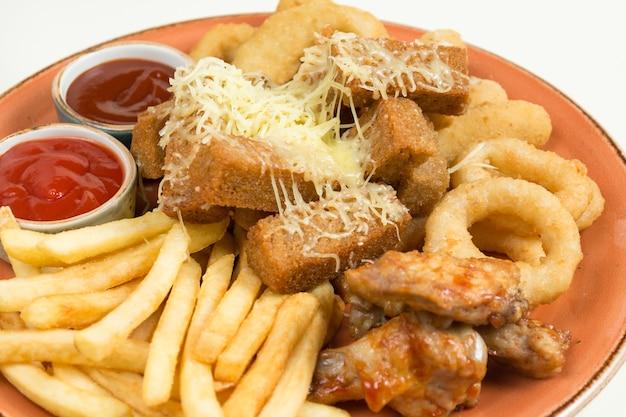 Patatine fritte, anelli di cipolla, ali di pollo, fette biscottate, uno spuntino alla birra su un piatto grande con due salse su fondo marrone.