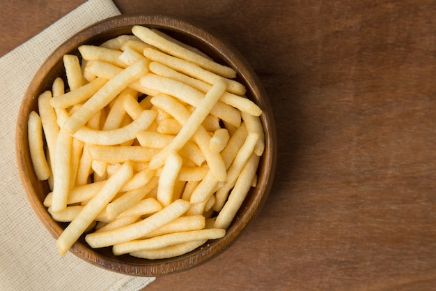 Patatine fritte o patate friggere in ciotola di legno mettendo su lino e fondo in legno.