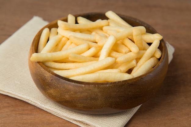 Le patate fritte o la patata friggono in ciotola di legno su fondo di legno.