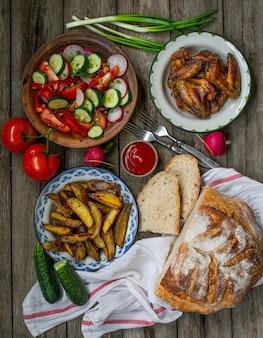 Patatine fritte, ali, insalata, verdure, pane su un vecchio fondo di legno. cena rurale, picnic estivo. vista dall'alto. disposizione piatta.