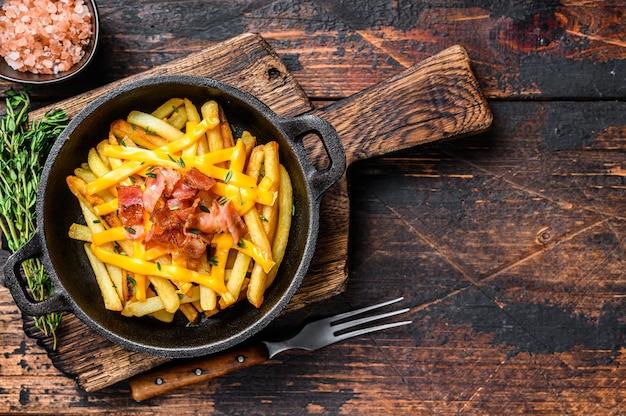Patatine fritte con mix fuso di formaggio cheddar e pancetta servite in padella. fondo in legno scuro. vista dall'alto. copia spazio.