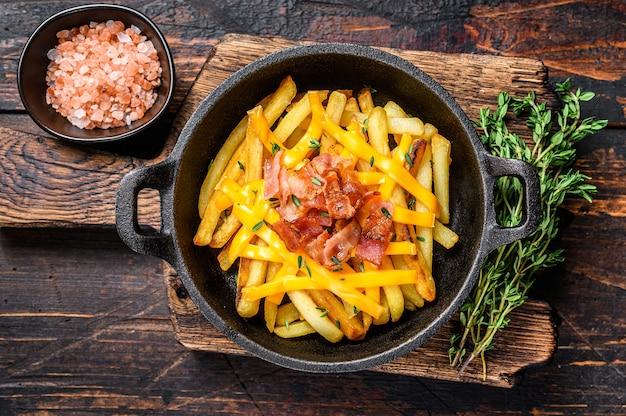 Patatine fritte con mix fuso di formaggio cheddar e pancetta servite in padella. tavolo in legno scuro. vista dall'alto.