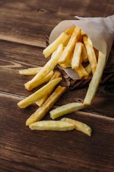 Patatine fritte su fondo di legno