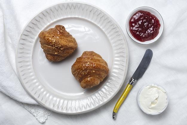 Croissant freschi fatti in casa francesi sulla tavola bianca con marmellata e burro