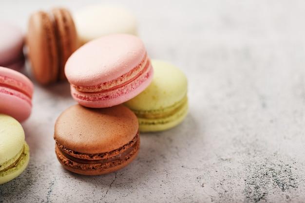 I biscotti macaron francesi di diversi colori sono sul tavolo grigio