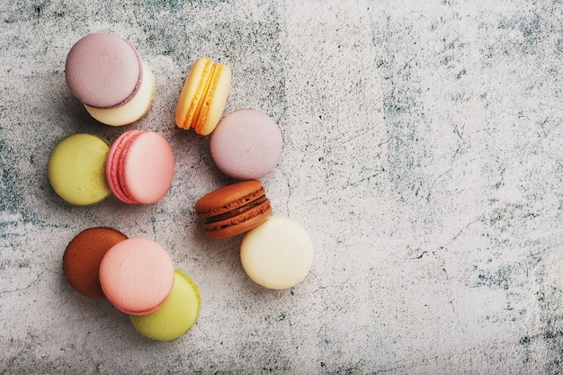Biscotti francesi di maccheroni di diversi colori sono sul tavolo grigio. natura morta di pasticceria.