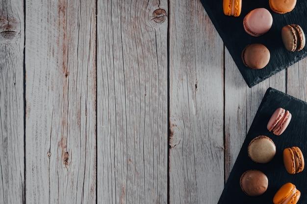 Biscotti macarons francesi in colori pastello su vassoio di ardesia copia spazio