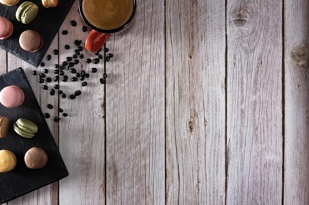 Dessert francese di macarons con tazza di caffè e chicchi di caffè copia spazio